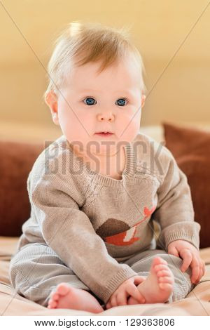 Cute little child with blond hair and blue eyes wearing knitted sweater sitting on sofa and touching her leg. Happy childhood