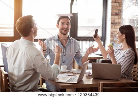 Joyful mood. Cheerful content playful colleagues sitting at the table and having fun while resting together