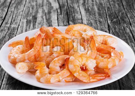 boiled tails of king shrimps on a white platter on an old rustic table close-up studio lights