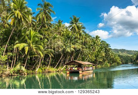 traditional raft boat on a jungle green river Loboc at Bohol island of Philippines