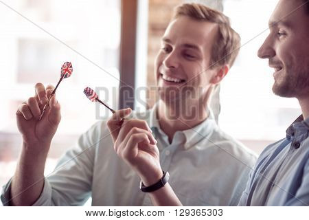 Nice device. Cheerful delighted handsome friends holding darts and smiling while going to play