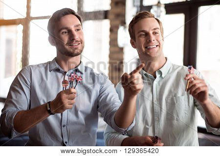 Have some entertainment. Positive handsome delighted smiling friends playing darts and expressing joy while spending time together