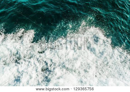 Rolling sea waves, top view of ocean covered by foam, turquoise and green color water