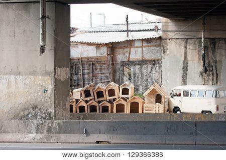 Pile of wooden dog houses near kombi car under bridge
