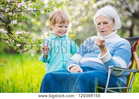 Senior woman showing something in hand to great grandson while relaxing in orchard