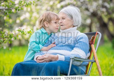 Little boy telling a secret to his great grandmother in a blossoming orchard