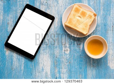 White display Tablet Toast Honey on blue wooden floor.