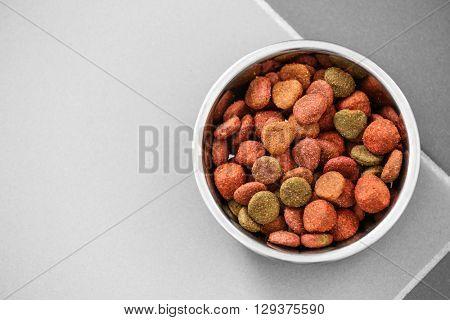 Pet food in a metal bowl on a floor.