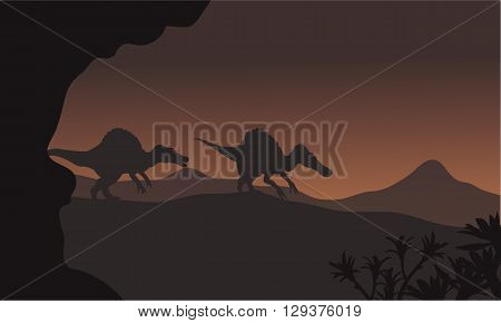 Silhouette of two spinosaurus walking in hills at night