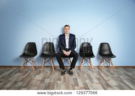 Young man in suit sitting on chair and waiting for job interview