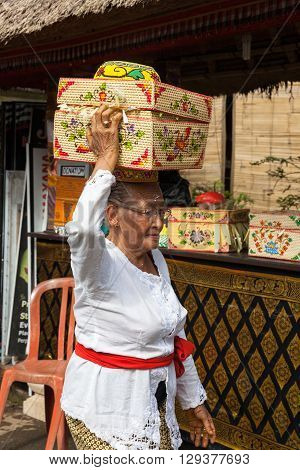 UBUD INDONESIA - MARCH 2 2016: Senior woman with basket on the head during the celebration before Nyepi (Balinese Day of Silence) on March 2 2016 in Ubud Indonesia.