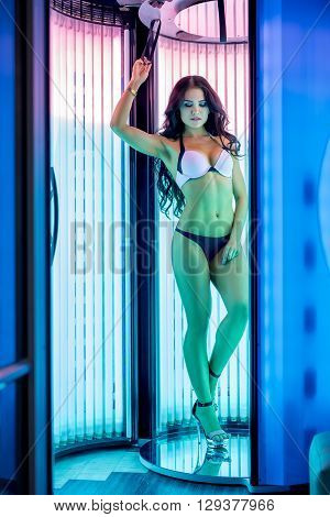 Image of beautiful brunette tans in modern tanning booth