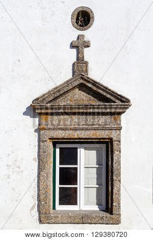 Window in Marvao decorated with a triangular pediment and a cross. Portalegre District, Alto Alentejo, Portugal. Marvao was a candidate to World Heritage Site by UNESCO.