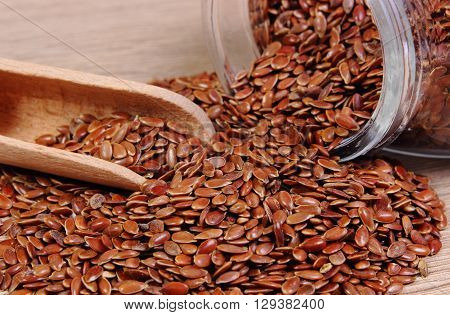 Heap of brown linseed flax seeds spilling out of glass jar on wooden background concept for healthy nutrition