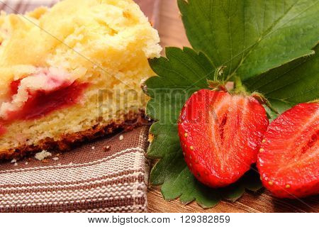 Fresh red strawberries with green leaves and piece of fresh baked yeast cake with crumble lying on wooden surface concept of dessert