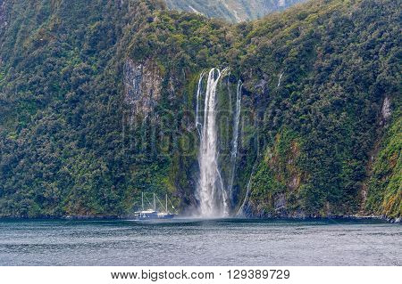 Milford Sound New Zealand - November 14 2014: The Milford Mariner Ship near high waterfall at Milford Sound Fjord New Zealand.