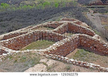 Stone walls from ancient Indian ruin in Northern Arizona extending downhill with green  trees in the background