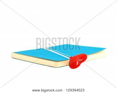 Red heart on the open blue book isolated on white background, select focus.