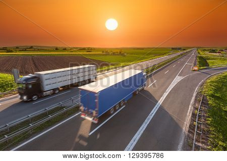 Two new trucks for different purposes driving towards the sun. Fast blurred motion drive on the freeway at beautiful sunset. Freight scene on the motorway near Belgrade Serbia.