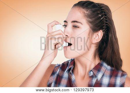 Woman having asthma using the asthma inhaler against orange vignette