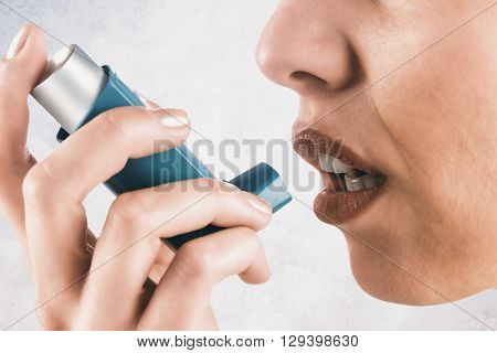Close up on an asthmatic woman against grey background