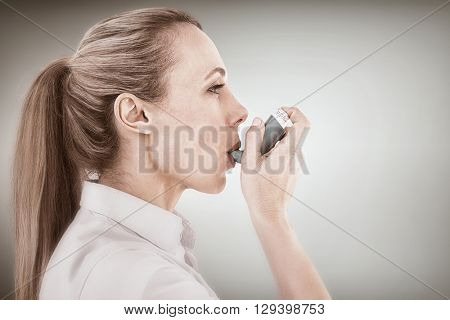 Pretty blonde using an asthma inhaler against blue vignette background