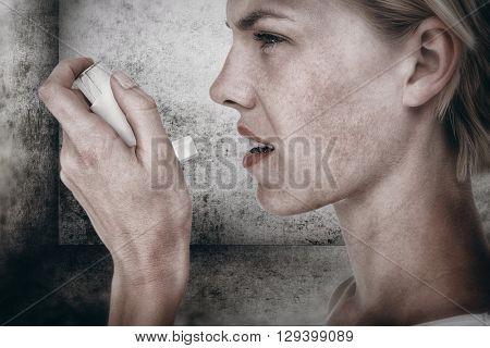 Asthmatic pretty blonde woman using inhaler against image of room corner