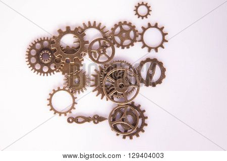 Metal clock gears and hand clock on the white background