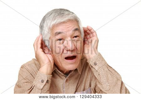 portrait of senior Japanese man with hand behind ear listening closely on white background