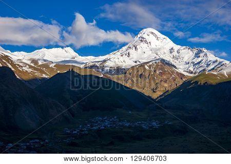 View of Kazbegi mountain and Stepantsminda village at sunrise