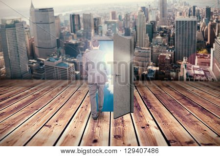 Young businessman walking away from camera against wooden planks