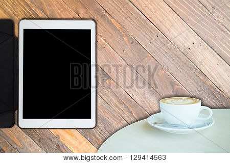 White cup of coffee and tablet on wooden backgound stock photo