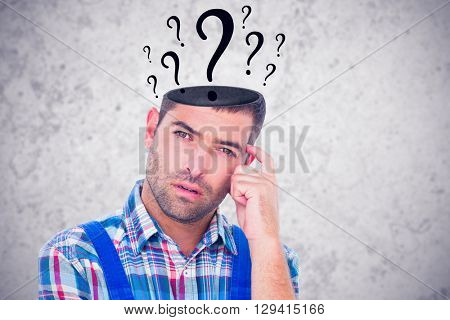 Portrait of confused manual worker scratching head against grey background
