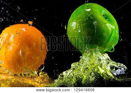 Fruits are bouncing on water surface on black background.