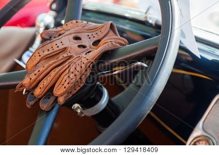 Color image of some vintage leather gloves on a car's steering wheel.