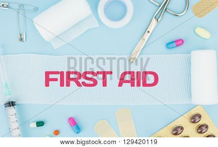 Medical Equipment, On Light Blue Background With First Aid Text On Unrolled Gauze