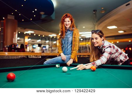 Two female friends playing billiards in a club