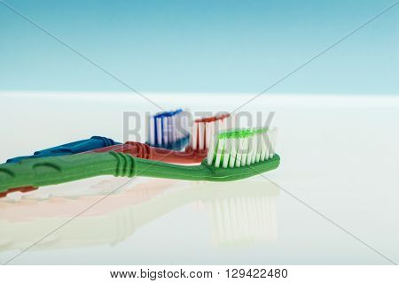 Three Toothbrushes On Reflecting Surface And Light Blue Background