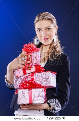Happy smiling yong woman holding many gifts decorated by red ribbons, birthday concept