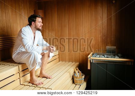 Handsome man relaxing in sauna during wellness weekend