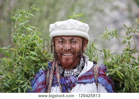 TURTUK VILLAGE, Jammu & Kashmir, INDIA - APRIL 221, 2016:   An unidentified Balti man in traditional dress is carrying willow twigs and branches