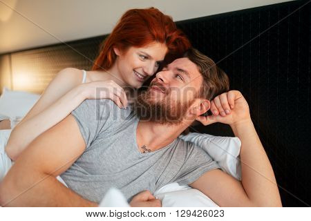 Sensual couple in bed cuddling and smiling