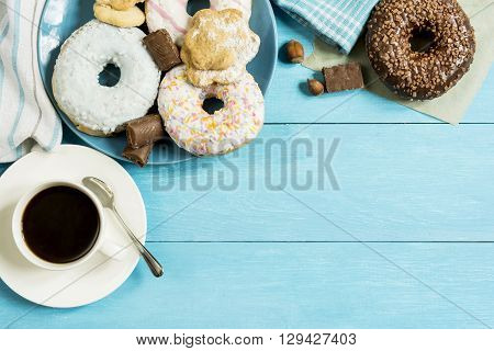 donut breakfast biscuits coffee and crockery on a wooden table view
