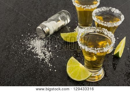 Shots of gold tequila with lime and salt on the black background. Tequila shot. Gold Mexican tequila. Tequila.