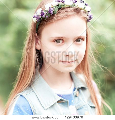 Beautiful teenager girl 12-14 year old wearing flower hairband outdoors. Looking at camera.