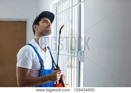 Thoughtful pest worker with sprayer looking up while standing at home
