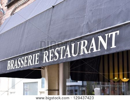 Brasserie restaurant, close-up of the building exterior of an old restaurant awning with white letters.