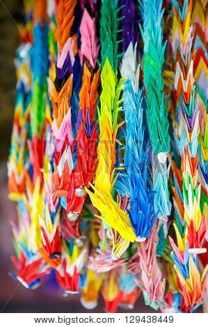 Colorful paper crane birds hanging together using fishing lines. Japanese origami in a temple in Japan.