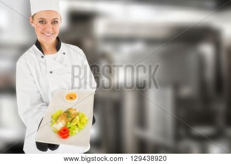 Female chef offering healthy food against pots standing on hotplate