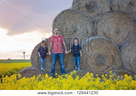 Father Andtwo Children, Boy Brothers In A Oilseed Rape Field, Sitting On A Bale Of Haystacks